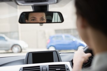 Woman driving with her reflection in the mirror