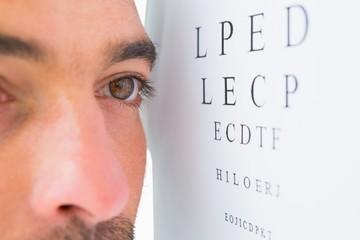 Focused man on eye test letters