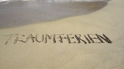 Wort Traumferien in Sand gezeichnet wird von Wellen weggespült