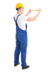 back view of man builder in blue uniform holding measure tape is