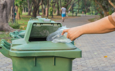Hand throwing bottle in trash cans
