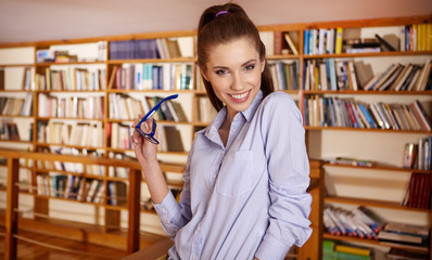 Portrait of a beautiful student in a library