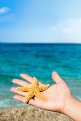 Woman holding starfish in his hand on the sandy beach