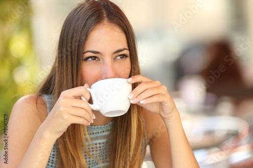 Woman drinking a coffee from a cup in a restaurant terrace - 78047419
