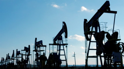 row of many working oil pumps silhouette