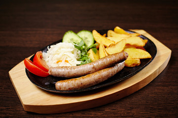 Roasted sausages in a frying pan on wooden table