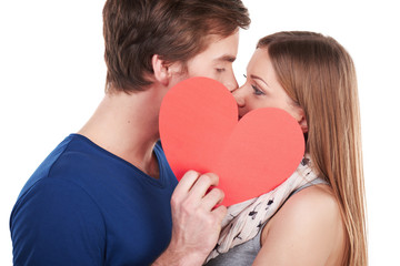 Woman and man kissing behind red heart