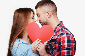 Young couple is kissing behind red heart