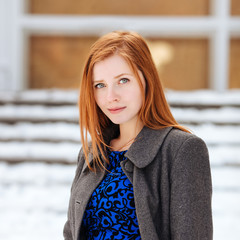 Young beautiful redhead woman posing at winter outdoors