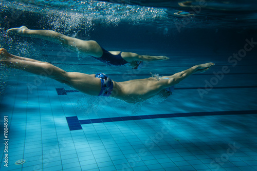 Swimmers at the swimming pool.Underwater photo.