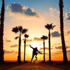 man jumping on skateboard near the ocean in sunset