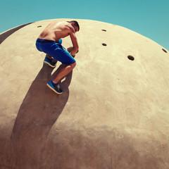 Athletic man climbing concrete wall