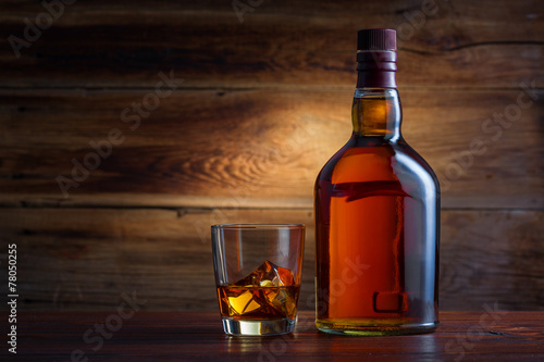 Bottle of whiskey on a wooden background - 78050255