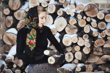 Attractive blonde woman on winter veranda on firewood background