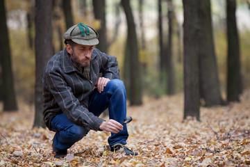 Man detective with a beard exploring footprint on the autumn lea
