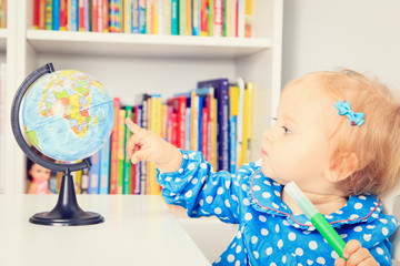little girl pointing to world globe in classroom