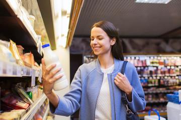happy woman holding milk bottle in market