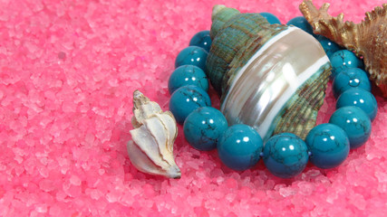 Three different sea shells on pink and turquoise beads