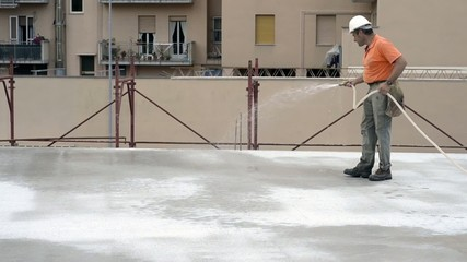 Construction worker watering fresh concrete slab using a hose