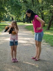 Mother scolding crying little girl in the park