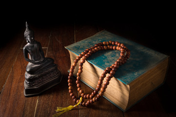 Buddha statue with necklace and antique book.