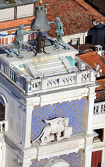 venice clock tower with blackened statues and winged lion