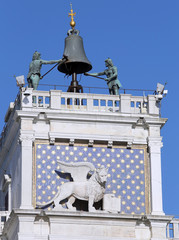 venice famous clock tower with blackened statues from the elemen
