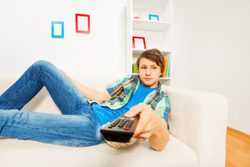 Boy switches remote control laying on white sofa