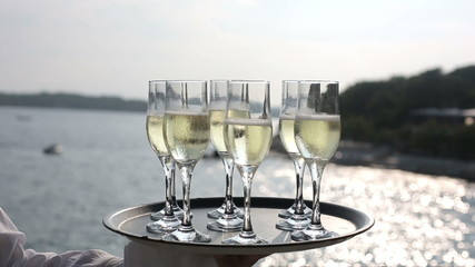Tray glasses champagne hands waiter at sea at sunset
