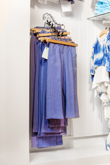 Blue trousers and jeans hanging in the shop