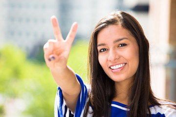 Happy, successful young woman showing v sign