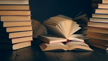 Old books on wooden deck table and dark background