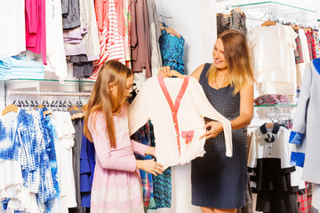 Girl and her mother shopping together in the store