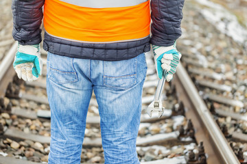 Worker with adjustable wrench on the railroad in winter