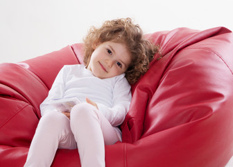 the child sitting on the furniture frame less isolated on white