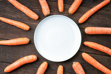 Carrots around white dish on wooden table
