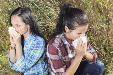 A Young woman sneezing in a field. Concept: seasonal allergy.