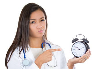 Unhappy young female doctor, nurse holding an alarm clock