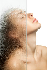 Woman washes her head behind a weeping glass shower door