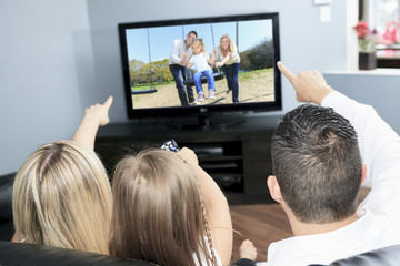 A Young family watching TV together at home