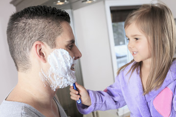 A Father with his daughter to shave in bathroom