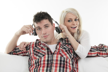 A cheerful couple sharing music in sofa at home