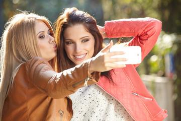 Friends making selfie. Two beautiful young women making selfie