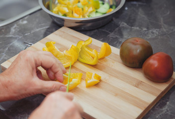 Female hands of an elderly woman cut pepper for salad