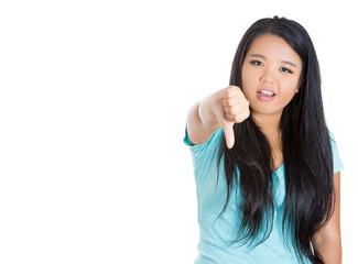 Unhappy woman giving thumbs down gesture looking displeased