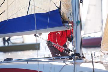 Member of sailing regatta stands at the mast
