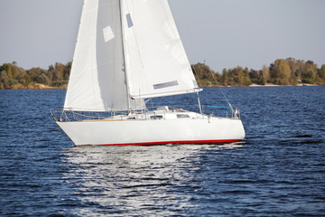 Sailing yacht at the river bank in autumn