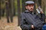 Man with a beard sitting in the autumn forest with a flask in hi