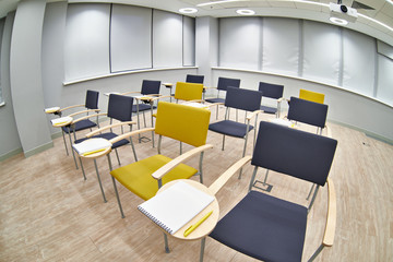 Chairs with notepads in empty classroom