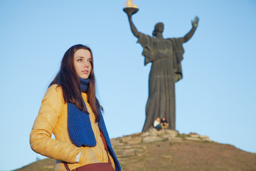 Young girl dressed in Ukrainian national colors against blue sky